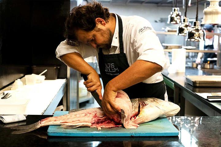 Chef João Rodrigues limpiando pescado