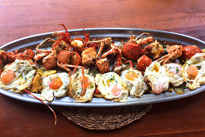 Lobster with fried eggs and Ibiza potatoes. Restaurant Cala Bassa