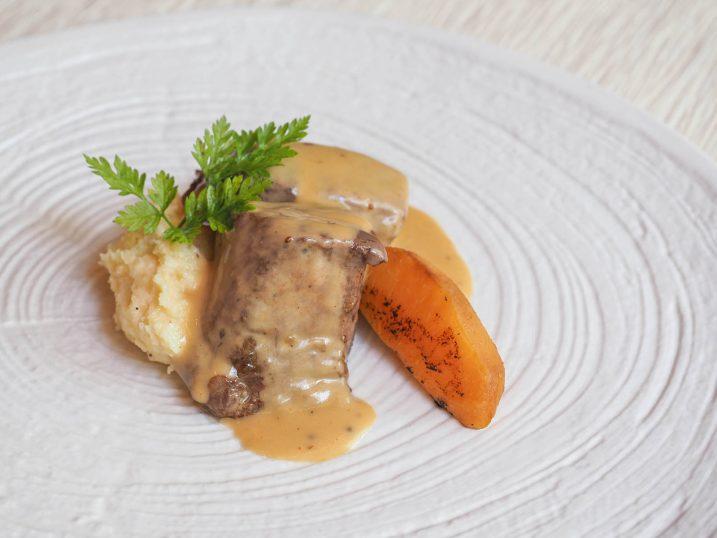 Carrillera de atún con salsa café de París con polenta y melocotón asado